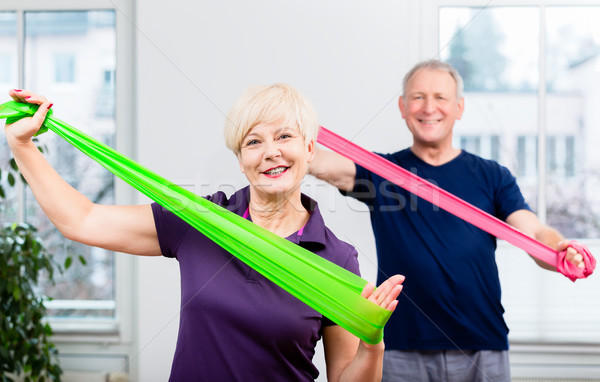Elderly couple in senior gymnastic class doing workout with rubb Stock photo © Kzenon