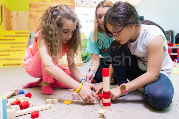 Two girls playing together with wooden toy blocks on the floor d Stock photo © Kzenon