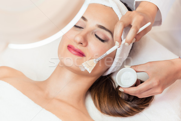Close-up of a beautiful woman relaxing during facial treatment in beauty center Stock photo © Kzenon