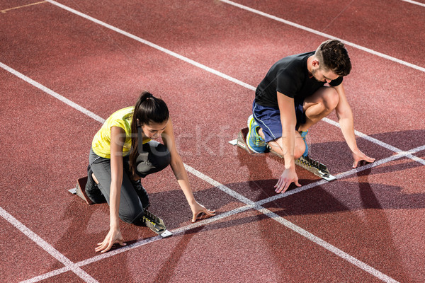 Male and female athlete in starting position at starting block Stock photo © Kzenon