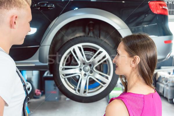 Beautiful woman looking happy at a reliable auto mechanic Stock photo © Kzenon