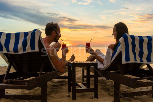 Young couple drinking cocktails on a beach at sunset during vacation Stock photo © Kzenon