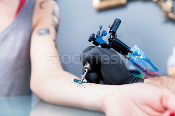 Close-up of the hand of a tattoo artist shading a colorful butterfly Stock photo © Kzenon