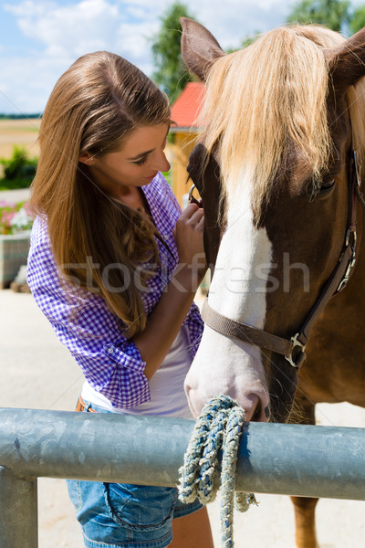 Young woman in the stable with horse at sunshine Stock photo © Kzenon