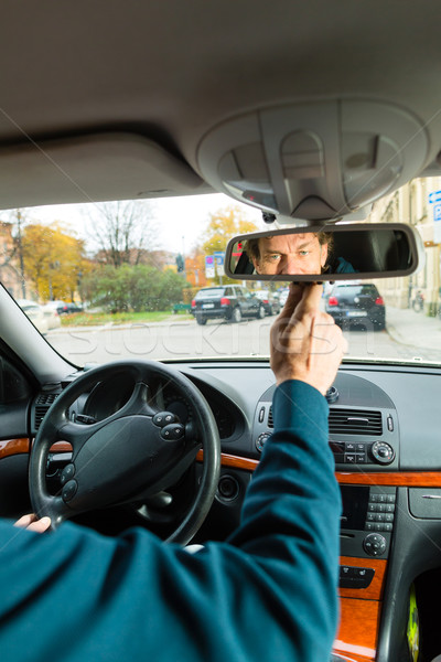 Taxi driver is looking in the driving mirror Stock photo © Kzenon