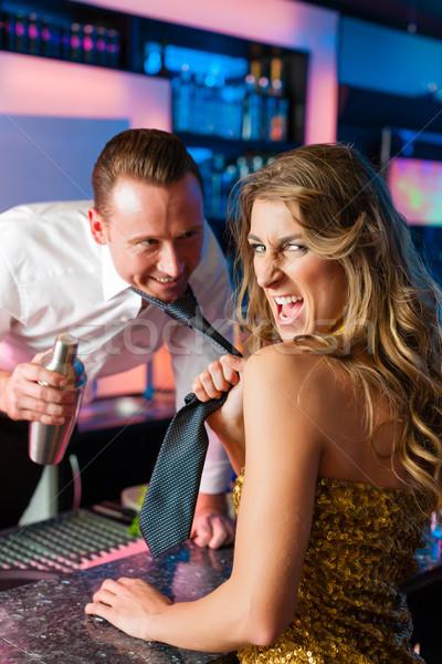 Woman dragging barkeeper in club or bar Stock photo © Kzenon