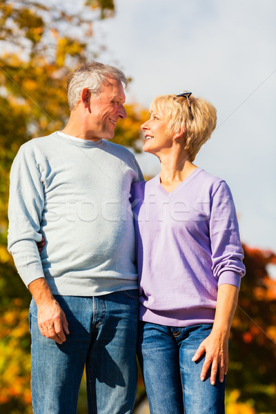 Seniors in autumn or fall walking hand in hand Stock photo © Kzenon