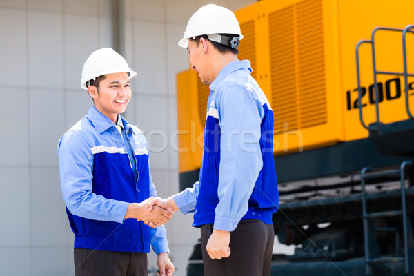 Asian engineers having agreement on construction site Stock photo © Kzenon