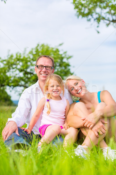 Family sitting on grass of lawn or field Stock photo © Kzenon