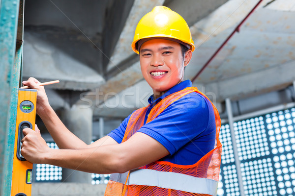 Builder or worker controlling wall on construction site Stock photo © Kzenon