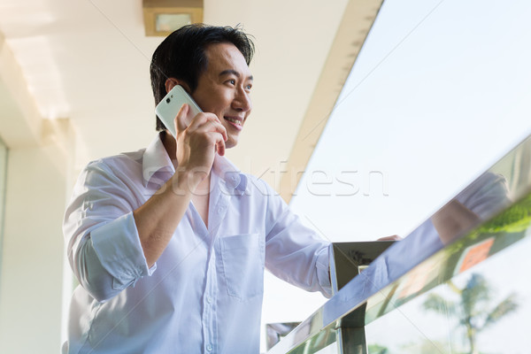 Asian man telephoning on balcony with mobile phone Stock photo © Kzenon