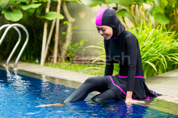 Muslim woman wearing Burkini swimwear at pool Stock photo © Kzenon