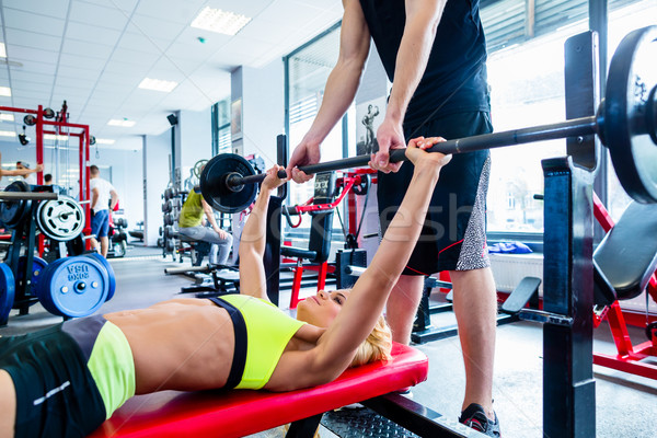 Woman with personal trainer at bench press in gym Stock photo © Kzenon