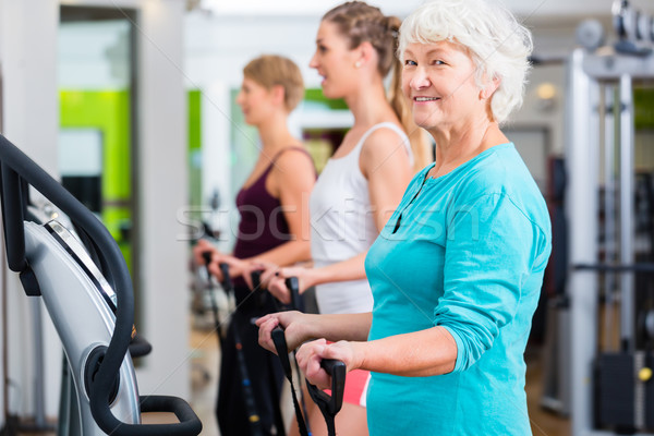 Old and young people on vibrating plates in gym Stock photo © Kzenon