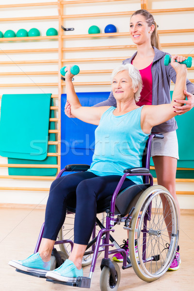 Senior woman in wheel chair doing physical therapy Stock photo © Kzenon