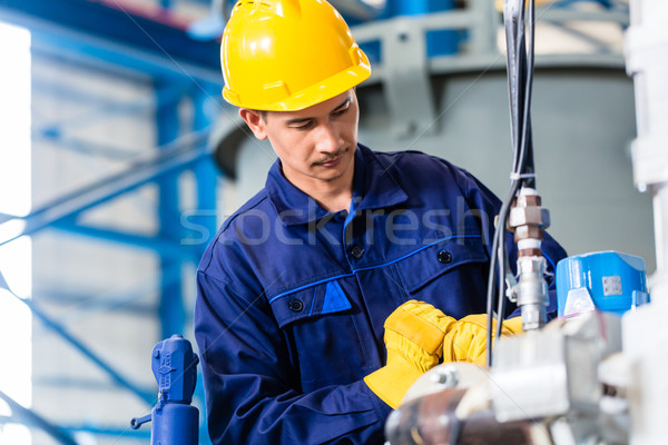 Technician in factory at machine maintenance Stock photo © Kzenon