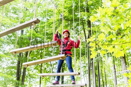 Kid walking on rope bridge in climbing course Stock photo © Kzenon
