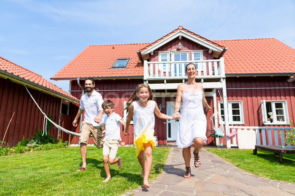 Happy family running on meadow in front of house Stock photo © Kzenon