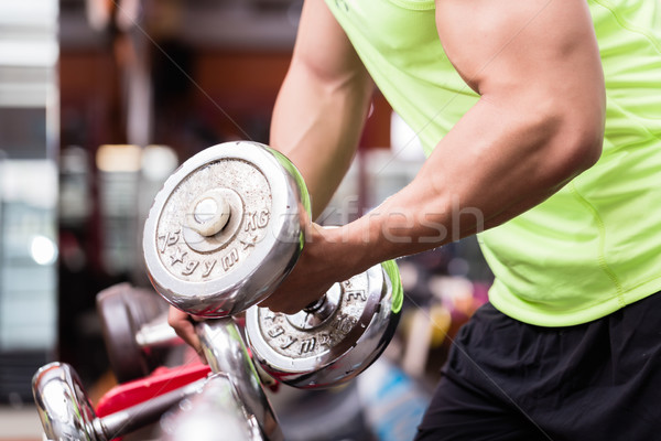 Man bodybuilder lifting weights during workout Stock photo © Kzenon