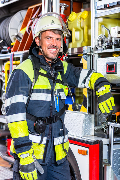 Fire fighter in protective clothes leaning at fire engine Stock photo © Kzenon