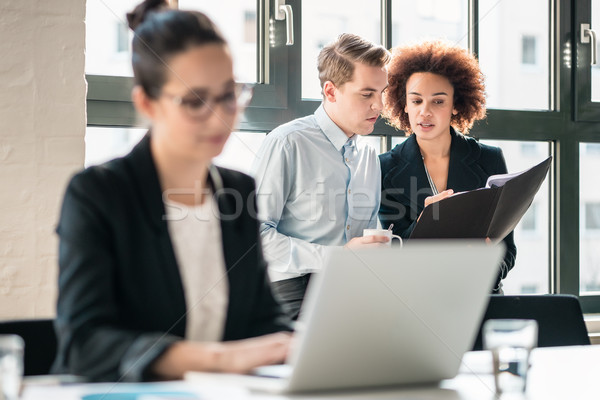 Two young malicious employees gossiping about their colleague Stock photo © Kzenon