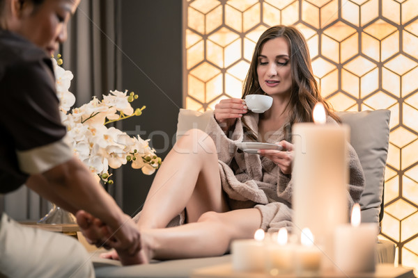 Young woman drinking tea during traditional Balinese foot massag Stock photo © Kzenon