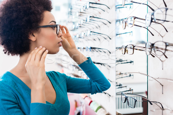 Black woman trying on glasses in optician store Stock photo © Kzenon