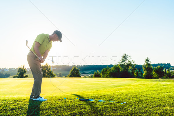 Experienced male golfer hitting the golf ball towards the cup du Stock photo © Kzenon