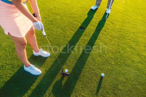woman player ready to hit the ball into the hole at the end of a Stock photo © Kzenon