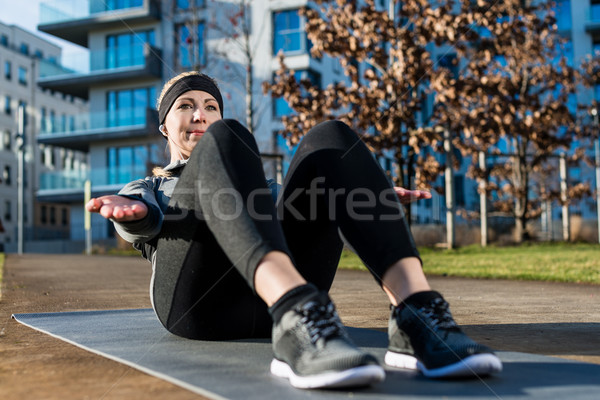 Young woman doing crunches with raised up palms for the abdomina Stock photo © Kzenon