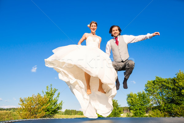 Stock photo: Bridal pair jumping outside on trampoline