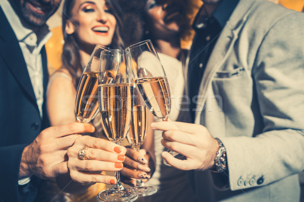 Men and women celebrating party while clinking glasses with spar Stock photo © Kzenon