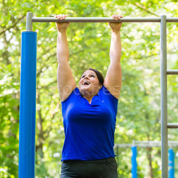 plump woman making sport exercises at high bar Stock photo © Kzenon