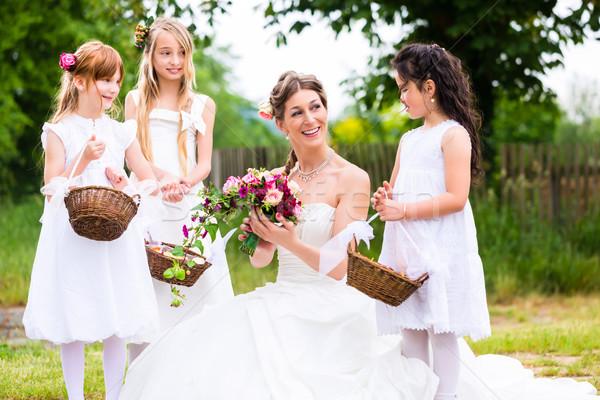 Bride in wedding dress with bridesmaids Stock photo © Kzenon