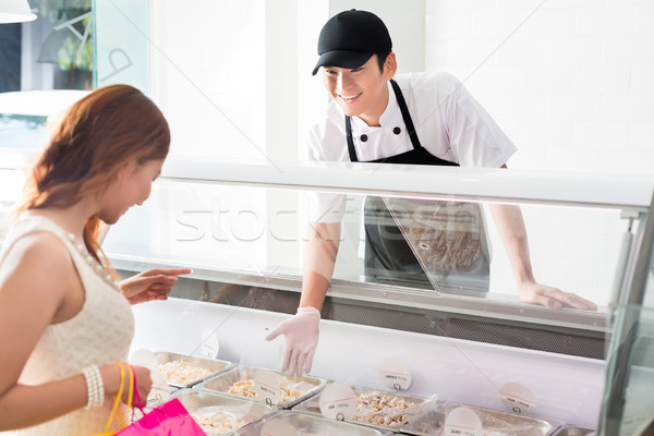 Young deli assistant serving a customer Stock photo © Kzenon