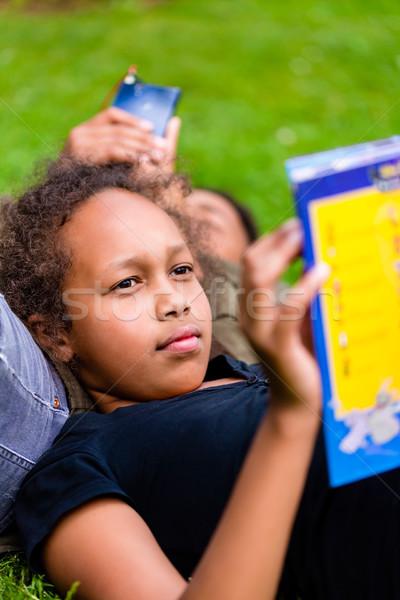Black girl reading book on meadow Stock photo © Kzenon