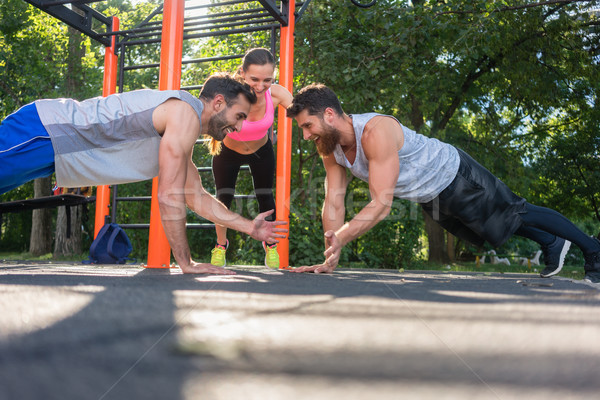 Stock photo: Two young men clapping hands from plank position during partner workout in park
