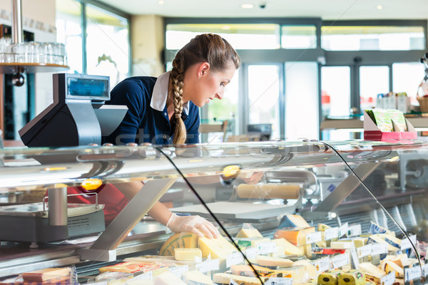 Woman in butcher shop putting sausage and meat on sale Stock photo © Kzenon
