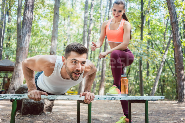 Sporty man doing push-up in an outdoor gym Stock photo © Kzenon