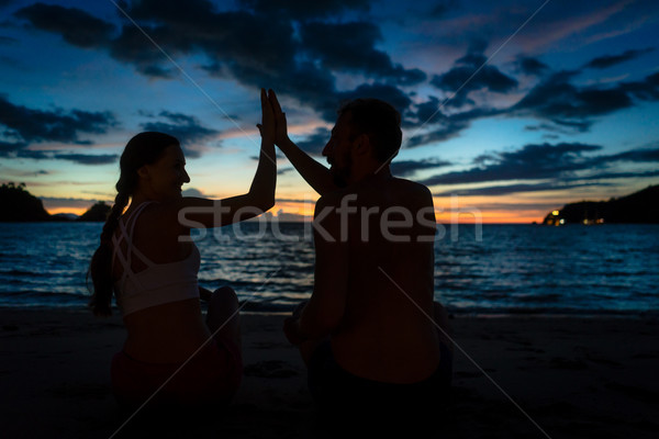 Cheerful young couple giving high five while sitting on a tropical beach Stock photo © Kzenon