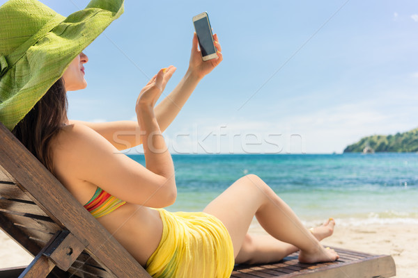 Attractive young woman sending a love message through a selfie on the beach Stock photo © Kzenon