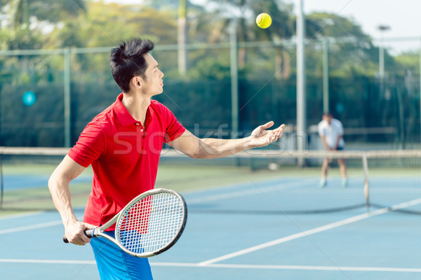 Chinese tennis player ready to hit the ball while serving in a tennis match Stock photo © Kzenon