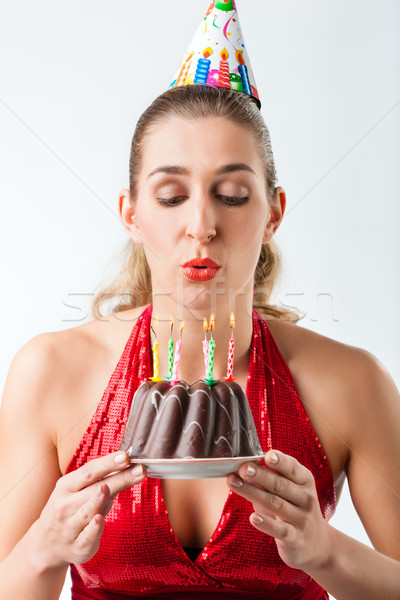 Woman celebrating birthday with cake blowing candles out Stock photo © Kzenon