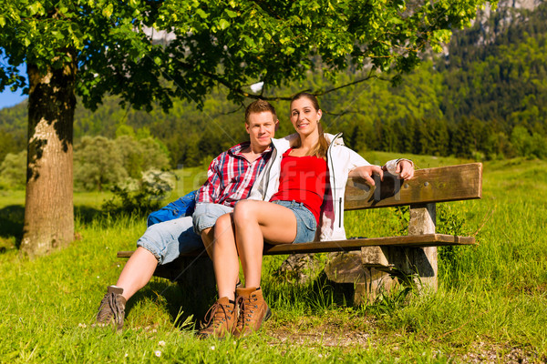 Happy Couple is sitting on a bank with mountain panorama Stock photo © Kzenon