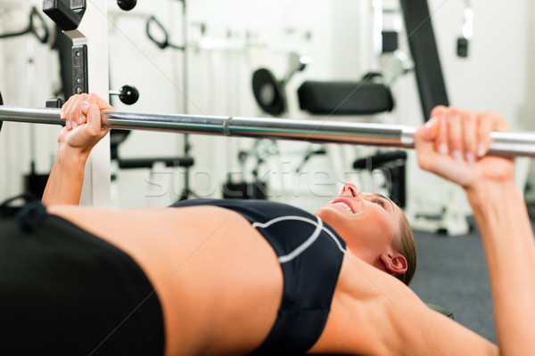 Woman in gym exercising with barbell Stock photo © Kzenon