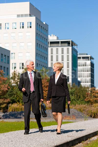 Uomini d'affari parlando esterna piedi parco business Foto d'archivio © Kzenon