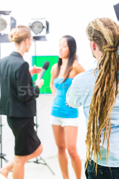 Cameraman shooting with camera on film set Stock photo © Kzenon
