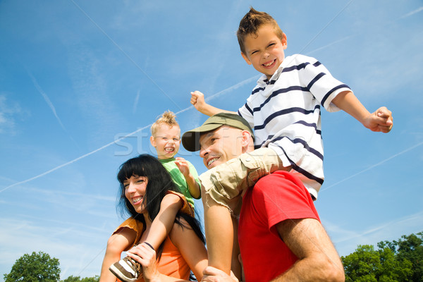 Blue sky família piggyback dois crianças Foto stock © Kzenon