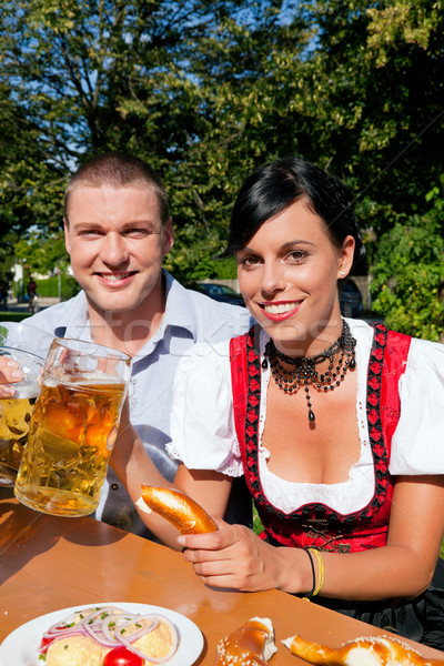 Couple in beer garden eating and drinking Stock photo © Kzenon