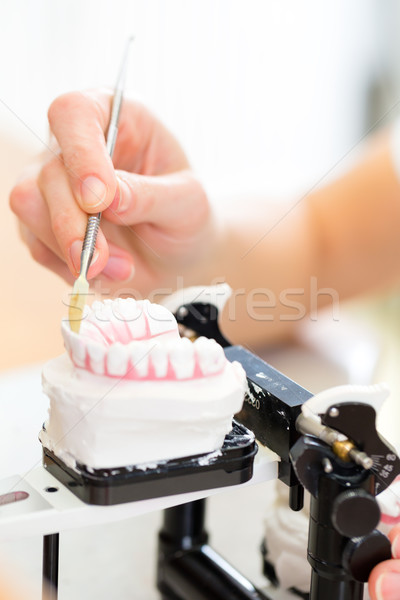 Dental technician producing denture Stock photo © Kzenon